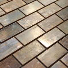 Medium Brick Antique Copper Mosaic Tile - This copper mosaic tile is made with real pieces of copper that have an antique finish. This mosaic features medium sized brick shaped copper tiles, because of the size of the individual pieces, this tile is suitable for wrapping around slightly rounded walls and other objects. The tiles in this sheet are mounted on a nylon mesh which allows for an easy installation.