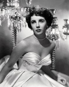 Elizabeth Taylor in a white, off-the shoulder ball gown, circa 1951.