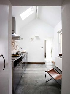 luminous white kitchen with skylights and concrete floor