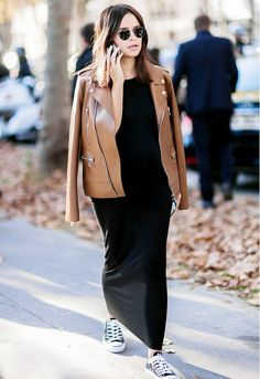 A fitted black maxi is worn with a brown leather jacket and converse.