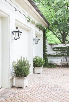 Though its design nods to history, the residence dates from the late 1990s. To quietly modernize, Anderson repainted selectively. Green garage doors look new with a fresh coat of white paint. Color comes in the form of fragrant rosemary planted in flanking stone pots.