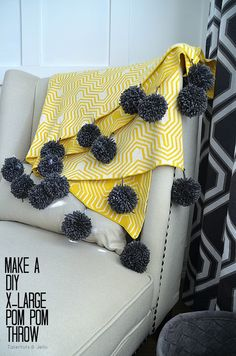 would be fun to attach to plain tablecloth.  She added two strings to tie off the poms and then cut one string short.  braided the remaining 3 to make the stronger then sewed the braid to the blanket.  Add clear nail polish to end of braid to prevent fraying.