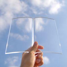 BOOK on BOOK は、好きな本の好きなページを開いたままにするために作られたアクリル製の透明な本です。使い方はシンプルお手元にある本のお気に入りのページを開きその上に BOOK on BOOK を乗せるだけ。5mm の厚いアクリルの重さで本を押さえながら非常に高い透明度のアクリル越しに本の内容を読む事ができます。写真集やアートブックを開いてインテリアに飾ったりお茶とお菓子を楽しみながら読書するなど様々なシチュエーションでお楽しみいただけます。本体の大きさはヨコ210mm × タテ185mm ×高さ20mm くらい。重さは220gです。文庫や新書にピッタリのサイズで作ってありますが本体が透明なので、大きな本に乗せたり、小さな本に乗せてもしっかり馴染みます。