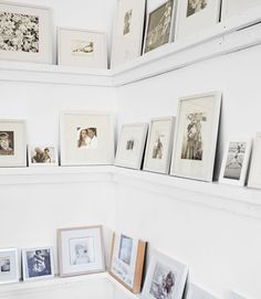 Gallery wall for family photos placed on shelving to avoid lots of nail holes & easy to switch out which photos you want to display....what if you used some kind of iron work...old fench?