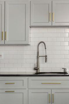 brass modern cabinet hardware gray cabinets black countertop white subway tile- Design Manifest