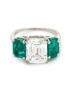 A Platinum, Diamond and Emerald Ring, containing one octagonal step cut diamond weighing approximately 3.07 carats and two octagonal step cut emeralds weighing approximately 2.00 carats total. #platinumdiamond