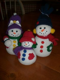 A snowman family I made from children`s socks filled with rice. Hats are made from inexpensive gloves. Felt scarves and mittens, Add pom poms. (Baby is made from 2 pom poms with a hat made from one cut off glove finger rolled up on edge.) Liquid app for facial features.