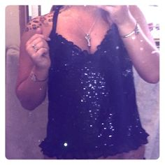 """Victoria's Secret Black Lace Sequined Top. Brand New. """"The Lacie"""" by Victoria's Secret.  Black lace spaghetti strapped mesh top adorned entirely in sequins!  Scalloped ruffled edging around the entire garment. Fun & flirty addition to any wardrobe, plus completely versatile for it can be worn out or double it as a sexy nightie to add to your sleepwear collection!  Adjustable straps. Never been worn, NWT.  Size Small.  Lace: 100% Rayon.  Mesh: 88% Nylon, 12% Spandex.  Ruffles: 86% Nylon…"""