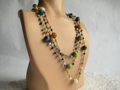 The colors in this necklace are gorgeous! It's made of tiny brass links each with a glass bead in the center. Made in a pattern of six tiny beads and then one large round one the chain is endless. Done in a rainbow of colors this necklace can be w...