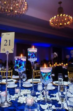 The reception decor is an icy array of blues and purples, featuring modern singular floral centerpieces and candlelit accents.