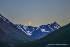 """""""The Posing Moon @ Midnight""""  This was the right place at the right time when the moon was about to set. This shot is taken at midnight in Alaska @ Denali National Park and Preserve. Its alignment between the snow clad mountains and the sky was just right. Personally feel this is a """"Lucky Shot""""."""