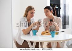 Two Female Friends Enjoying Breakfast At Home Together - stock photo