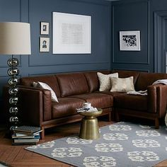 Love this leather sofa that will mix in the warm colors that you like but we can add some grey pillows to match the white on the wall. Definitely want to have a dark color on the wall facing the west where the media stand will live. #GreyPillow