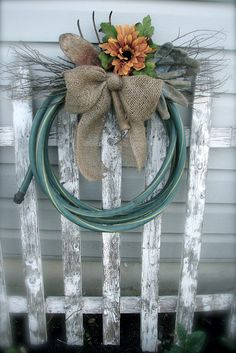 garden hose wreath for the shed.wrap an old garden hose into circular form, secure with wire, add some small dried branches, burlap bow and silk sunflower! Garden Crafts, Garden Projects, Diy Projects, Garden Tools, Diy Wreath, Door Wreaths, Wreath Making, Garden Hose Wreath, Burlap Bows