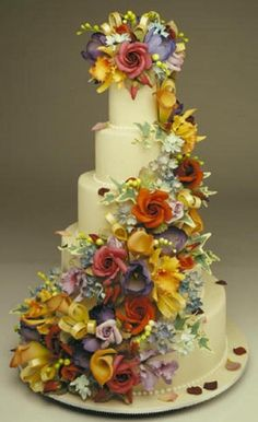 Pretty wedding cake with different colours of cascading flowers. ??b?