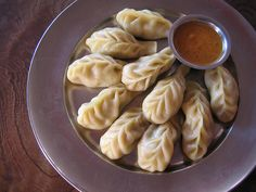 Momos (Nepal). 'These little meat- or vegetable-filled dumplings are Nepal's unofficial national dish. Enjoy them in one of Kathmandu's grandiose traditional Nepali restaurants, at a shared table with monks in a backstreet Tibetan kitchen or in a trekking lodge overlooking the Annapurnas – they are the quintessential taste of the Himalayas.' http://www.lonelyplanet.com/nepal