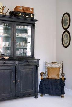 czarny kredens, walizki vintage i stylowe owalne ramki z fotografiami retro - Lovingit.pl