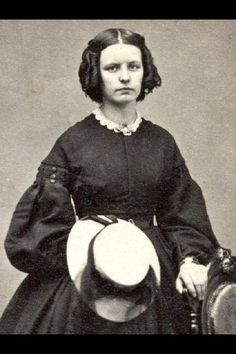 A young lady holding her hat in order to show off her girlish curls c. 1864