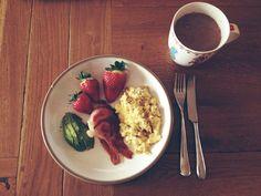 clean breakfast: scrambled eggs, smokey bacon, sliced avocado and strawberries