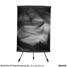 The Black Fire IV Tripod Lamp designed by Artist C.L. Brown features fire photography converted to black and white. Brighten up any room with this artist-designed tripod lamp for a statement piece that will add instant style to your home decor. Choose your trim and shade material for a special, one-of-a kind home or office accent. Choose from film polyester, rice paper, or linen lamp shades. Printed with state-of-the-art 14 color vibrant printing with fade resistant ink. Base is sturdy…