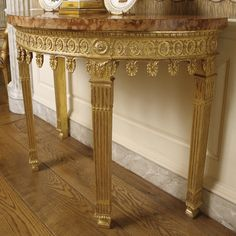 An important pair of George III giltwood and marble top pier tables circa 1775 almost certainly after a design by Robert Adam, each with a later rosso antico marble-veneered demilune top, each table with lamb's tongue-carved edge above a frieze carved with rosettes interspersed between gathered leaves and pendent palmettes, the breakfronted legs headed by rosettes above bucrania, beaded collars and long leaves continuing to fluted legs ending in long leaves above gadrooning and waisted…