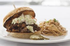 Hawaiian Style Kahlua Pulled Pork                                      with sassy slaw, pineapple coconut lime cream cheese on Village Bakery bun served with oriental noodles.