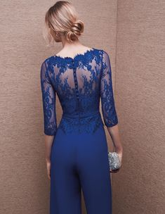 One-piece in blue georgette with straight, wide trousers. Sweetheart bodice and sheer lace overlay with bateau neckline. Elbow-length sleeves and narrow georgette belt at the waist.