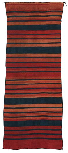 CLASSIC PUEBLO BLANKET, PROBABLY ACOMA finely twill-woven in handspun and ravelled bayeta wool, in shades of lac (?) and cochineal dyed red and rich indigo blue, with an overall banded design overlaid with stripes; three panels woven with a diamond-twill technique.
