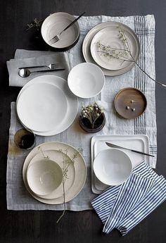 Ein wunderbar gedeckter Tisch von oben mit viel schönem Geschirr in Erdtöne.