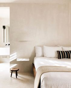 Minimal is better. Clay inspired walls with white linen bedding at the Casa Pueblo Tulum.