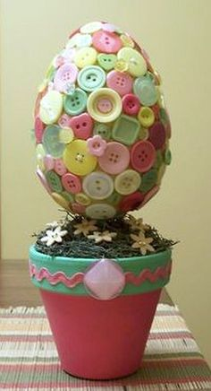 Styrofoam egg, a clay pot and lots of buttons.