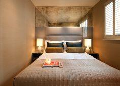 Блестящая панель в верхней части одной из стен узкой комнаты