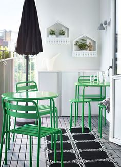 Balcone con due tavoli rotondi verdi, sedie e sgabelli verdi, ombrellone nero e tre mobili in acciaio bianchi