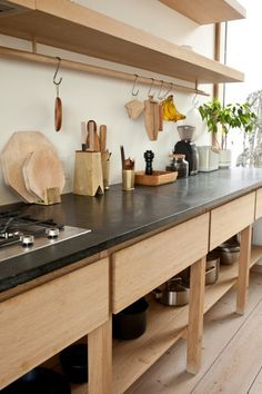 The counters are soapstone. Suspended from a custom oak rail are a Bagel Trivet(CA$80) and a Coffee Trough by Tomiyama Koichi ($150). On the counter, brass Utensil Holders by Oji Masanori (CA$200 for the small, CA$300 for the large) corral a set of kitchen tools.