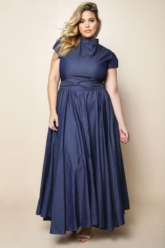 A charming plus size maxi dress, featuring a smooth fabric with a cool dark denim wash. Crafted with a mock neck, cap sleeves, and pleated skirt with a stunning drape. Comes with a self-tie belt to define the waistline. Finished hem. Zip-up back.