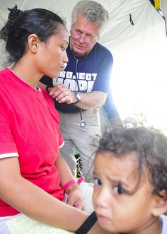 Project HOPE Volunteer Dr. Alan Jamison helping a woman and her child.