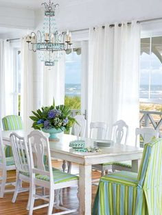 Mis-matched thrift store chairs are unified with a fresh coat of paint and candy-striped blue and green fabric. A chandelier adds glamour to the thrifty dining room. (Photo: Richard Leo Johnson)