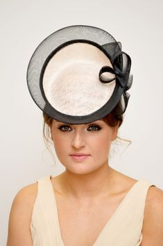Soft peach percher style headpiece from John Paul millinery with black trim detail and side bow.
