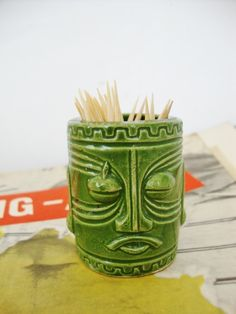 This green ceramic tiki head toothpick holder or shot glass is probably from the late 1950s or early 1960s. The size is 2 1/8 inches high by 1 5/8