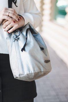 Bolsa saco prateada com detalhes pretos da Kipling.  Look de Outono com suéter branco da Zara com piscadinha, saia preta com botões na frente, meia calça e bota de verniz.