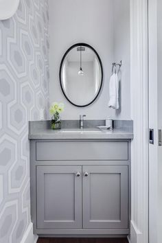 Small gray powder room features a gray washstand topped with gray quartz, Caesarstone Pebble, under a black twisted oval mirror next to an accent wall cla din gray hex wallpaper.