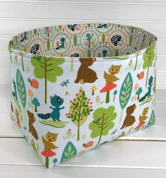 Stay neat and organized with this lovely and functional storage bin! This bin is a must have for any room of your home. The outside of this lovely bin has adorable woodland animals and trees on a light background. This storage bin measures 9 L x 6 W x 7 H (Please see last picture to help visualize size of bin.) There are layers of heavy interfacing to give this bin structure and shape. It is double stitched on stress points to ensure durability. Made with love in my smoke/pet free home. ...