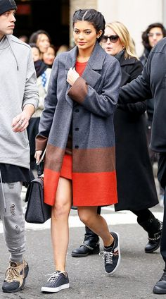 Kylie Jenner wears a t-shirt dress with an elevated coat, gray handbag, and sneakers