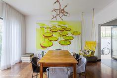 Sala de jantar tem mesa de madeiras com cadeiras tipo espaguete e balanço feito com cordas.