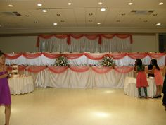 Ornate head table setting with white satin screens and draping on head table and stage accented with a reddish coral to match the bridesmaids dresses.