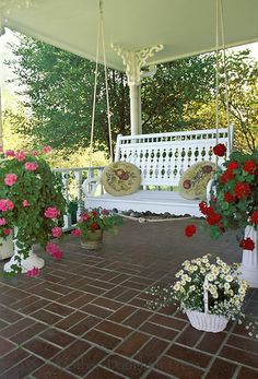 ❤ Brick tile front porch with hand made victorian wood painted swing with two hooked pillows and many potted plants.
