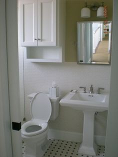 Over Toilet Storage plus black and white tiles and a pedestal sink