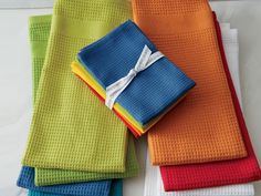 A set of brightly colored hand towels can perk up the kitchen for mere pennies. And you aren't limited to the oven door handle: hang interesting linens (aprons and oven mitts, too) from hooks or pegs on a floating wall shelf or line a wooden bowl on the countertop to add punch. Shown are waffle-weave Salsa dish cloths and towels from Crate & Barrel.