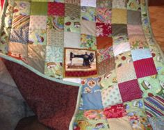 A lap quilt with a sewing theme. The antique sewing machine and whimsical pin cushions are adorable