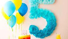 Decora con un número gigante la pared de tu fiesta de cumpleaños. Haz una plantilla con cartón y pégale pompones de papel. Será un fondo espectacular para la mesa de dulces. #ideasparafiestas #fiestas #cumpleaños